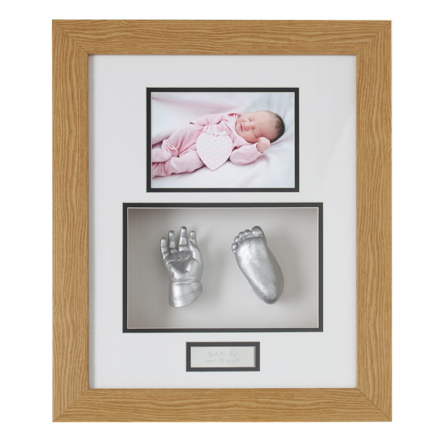 Silver baby hand and foot cast in a wood frame