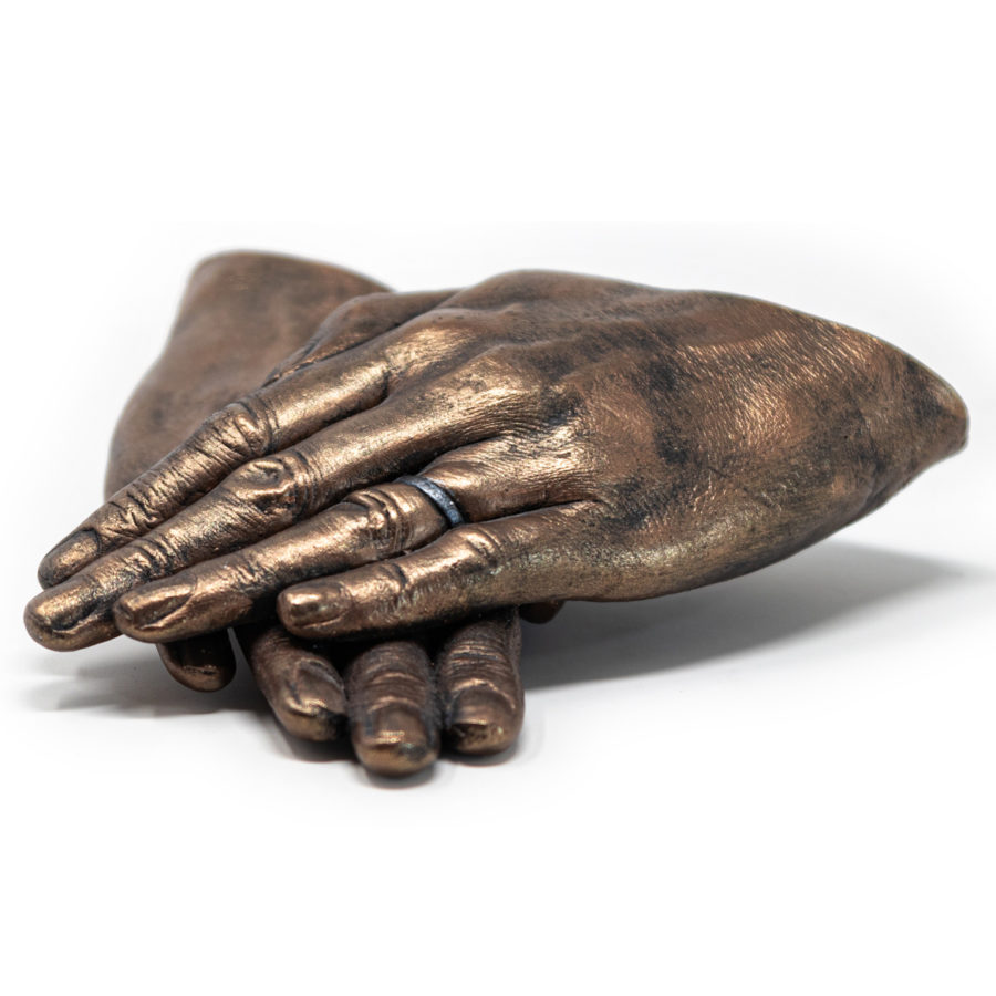Bronze hands laying on top of each other