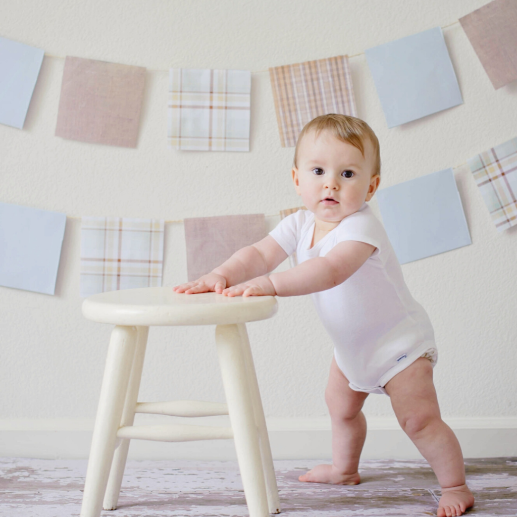 Baby leaning on a foot stool to stand