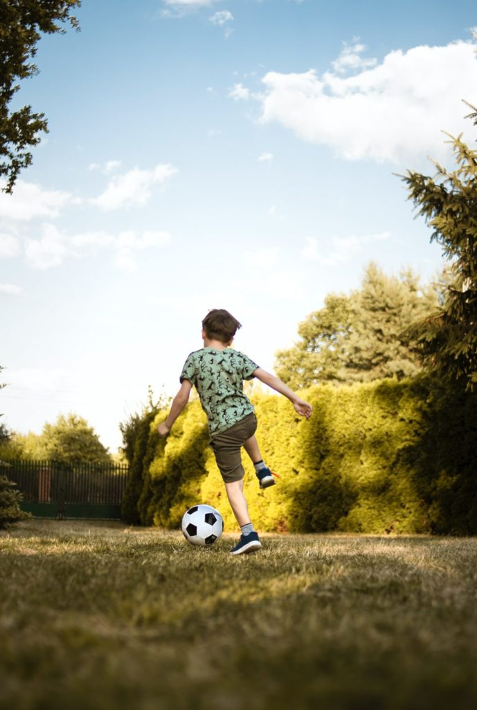a young boy plays football in his back garden