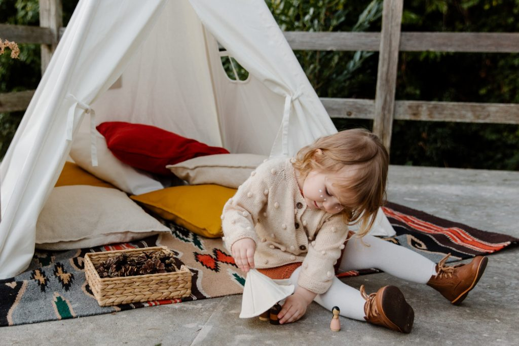 a small girl playing outside with her den
