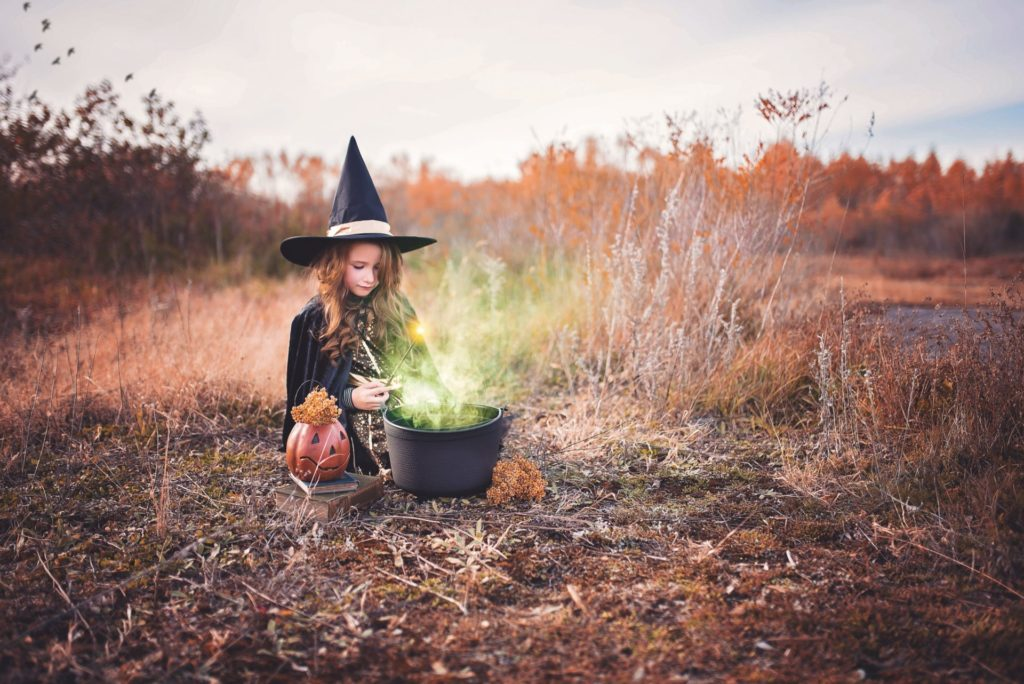 Child dressed as a witch with a pumpkin